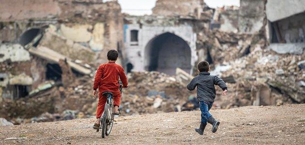 Zwei Kinder, eines fahrradfahrend, das andere rennend, bewegen sich vor einem Hintergrund zerstörter Gebäude und Trümmer.