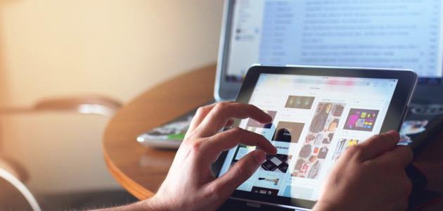 Zwei Hände bedienen einen Tabletcomputer; im Hintergrund leuchtet ein Notebookbildschirm