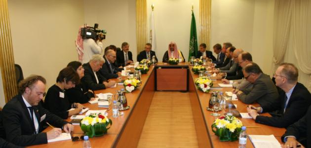 Das Foto zeigt einen Konferenztisch mit Menschen in arabischer und westlicher Kleidung, die an einem großen Konferenztisch sitzen.