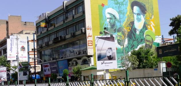 Das Foto zeigt, von einer Straße aus betrachtet, die Seitenwand eines Gebäudes, die ein großes Wandbild trägt, welches Ajatollah Chomeini und weitere bekannte Personen Irans zeigt; davor steht ein Werbeplakat für einen japanischen Uhrenhersteller.