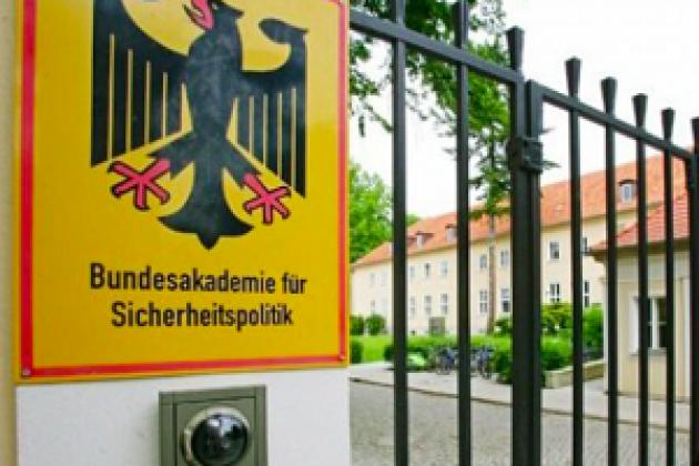 Blick auf ein Schild mit der Aufschrift Bundesakademie für Sicherheitspolitik. Das Schild hängt an einem zaun vor einem Gebäude.