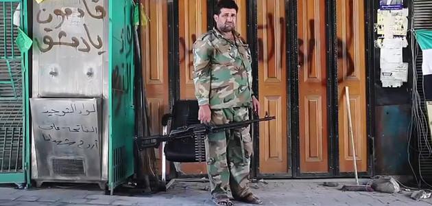 """Ein Kämpfer der \""""Freien Syrischen Armee"""", bewaffnet mit einem Maschinengewehr, vor einer verschlossenen, mit Graffiti besprühten, Ladenfront."""