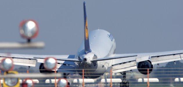 Ein Lufthansa-Jet landet auf einer Landebahn. Im Vordergrund sieht man die Landehilfe.
