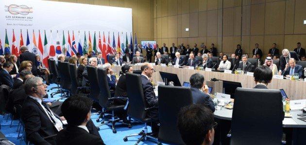 """Zahlreiche Außenminister der G20-Mitgliedsstaaten sitzen um einene großen Konferenztisch vor einer Pressewand mit der Aufschrift \""""G20 Germany\""""."""