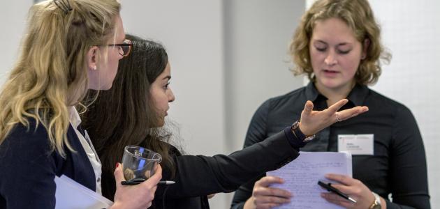 Drei geschäftlich gekleidete junge Frauen stehen beieinander und diskutieren.