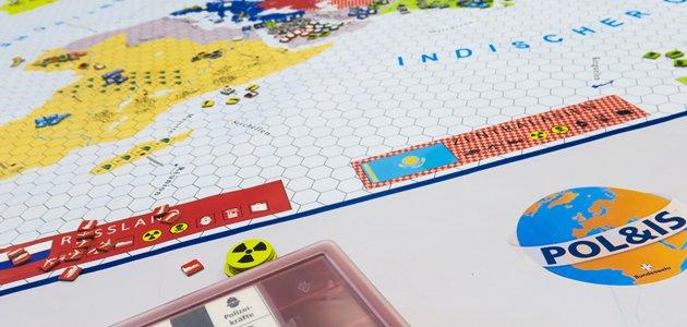 Das Bild zeigt die Welt Pol&IS als Spielbrett. Daneben liegen Spielkarten und Spiel-Chips mit aufgedrucktem Atomzeichen, rechts davon ist die Aufschrift Pol&IS zu lesen.