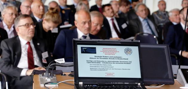 Im Vordergrund ein Laptop, im Hintergrund sitzende Menschen