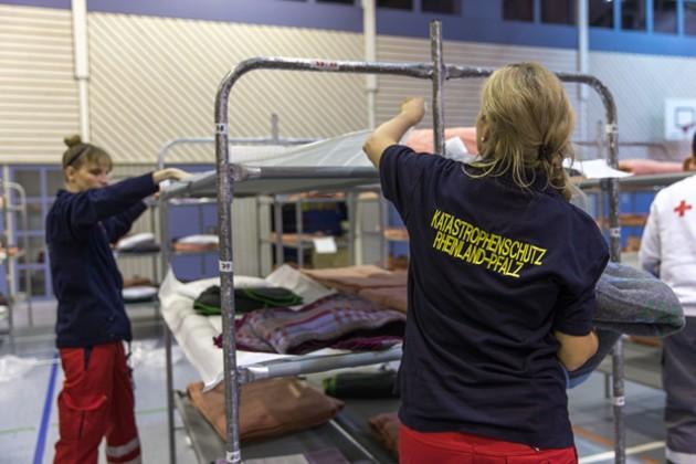 Zwei Mitarbeiterinnen des Katastrophenschutzes Rheinland-Pfalz stellen Betten in einer Notunterkunft auf.