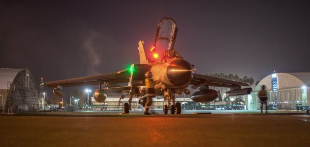 """Maintenance crews investigate the fighter jet \""""Tornado\"""" on the airfield between two hangars at the air base Incirlik on February 24, 2016."""