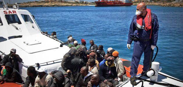 Flüchtlinge aus Afrika sitzen in einem Boot der italienischen Küstenwache; ein Angehöriger der Küstenwache steht am Bug und vertäut das Boot.
