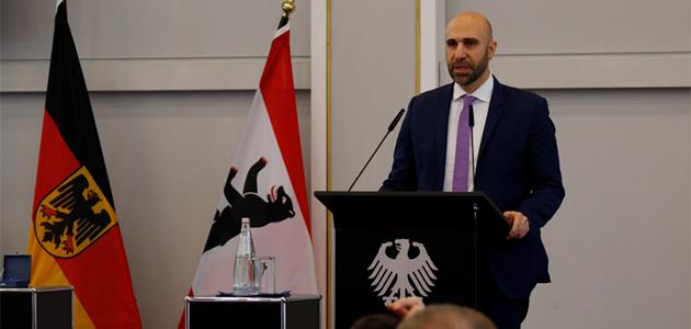 Ahmad Mansour steht sprechend an einem Pult mit dem Bundesadler darauf; links von ihm stehen die Bundesflagge und die Flagge Berlins.