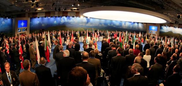 Zahlreiche Menschen stehen in einem zum Teil abgedunkelten Konferenzsaal mit Projektionen der NATO-Flagge an den Wänden.