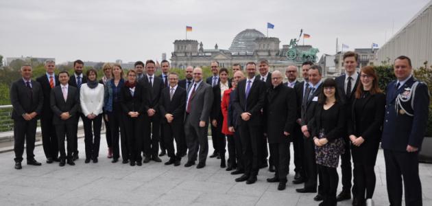 Eine Gruppe von Menschen steht auf dem Dach der US-Botschaft in Berlin; im Hintergrund ist der Deutsche Bundestag sowie davor die Quadriga auf dem Brandenburger Tor sichtbar.