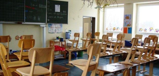 In einem Klassenzimmer stehen zahlreiche kleine Stühle und Tische aus Holz; an der Stirnseite des Raums steht eine beschriebene Tafel.