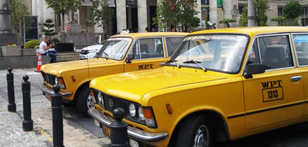 Im Vordergrund stehen zwei gelbe Taxis osteuropäischer Bauart; im Hintergrund ragt eine Säulenkollonade mit Plakaten zwischen den Säulen auf.