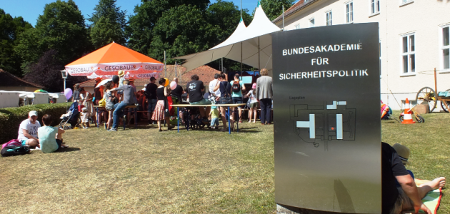 Auf der Wiese vor dem Haus Bonn der BAKS stehen Zelte und eine Menschenmenge, letztere zum Teil sitzend auf Bänken und dem Boden; rechts ragt das Haus selbst auf; im Vordergrund rechts steht ein großes Metallschild mti dem Namen der BAKS.