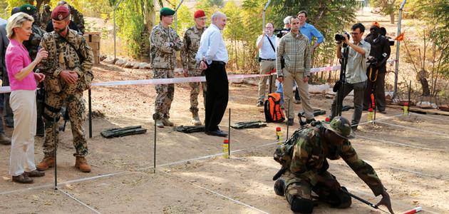 Verteidigungsministerin Ursula von der Leyen besucht die Pionierausbildung des deutschen Einsatzkontingent in Mali; links stehend die Ministerin im Gespräch mit einem deutschen Soldaten, rechts knieend ein malischer Soldat in einem Übungsminenfeld.