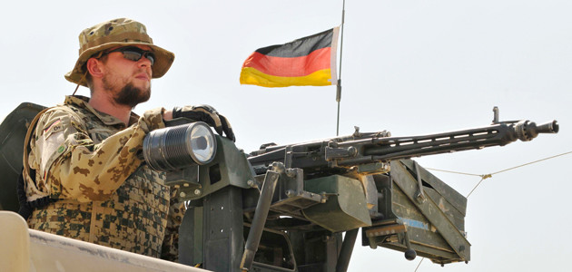 A German soldier of the Camp Marmal Force Protection Group mans a machine gun atop a vehicle, North Afghanistan, August 2011
