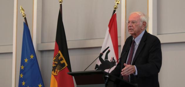 Ein geschäftlich gekleideter Mann steht an einem Rednerpult neben den Flaggen der EU, Deutschlands und des Landes Berlin und spricht in ein Mikrofon.
