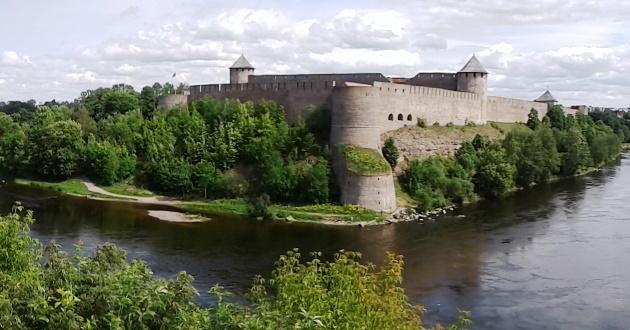 Eine Burg umgeben vorm Wasser vor bewölktem Himmel.