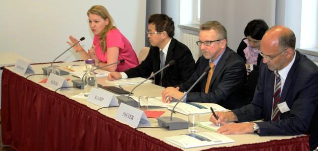 Vier Personen sitzen an einem Podiumstisch mit Mikrofonen; die Frau am linken Ende des Tischs spricht ins Mikrofon und gestikuliert.