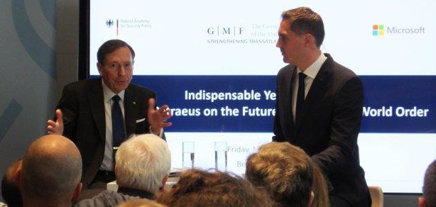 David Petraeus diskutiert vor einem Bildschirm, der die Logos der BAKS, des German Marshall Fund und Microsoft zeigt, mit dem Journalist Frederik Pleitgen.