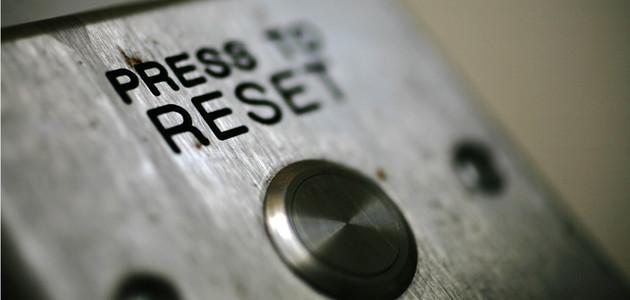 """Nahaufnahme eines Schaltknopfes auf einem Metallgehäuse, Beschriftung \""""Press to Reset""""."""