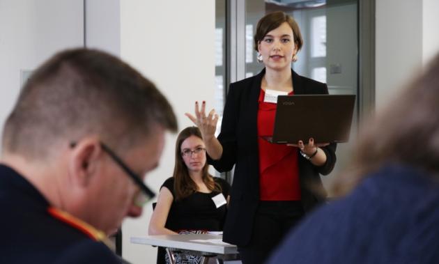 Eine Frau mit einem Notebook in der Hand spricht gestikulierend zu einem uniformierten Offizier.