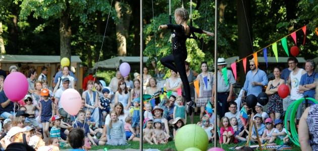 Eine junge Akrobatin führt im Freien vor einer sitzenden Menschenmenge Kunststücke auf.