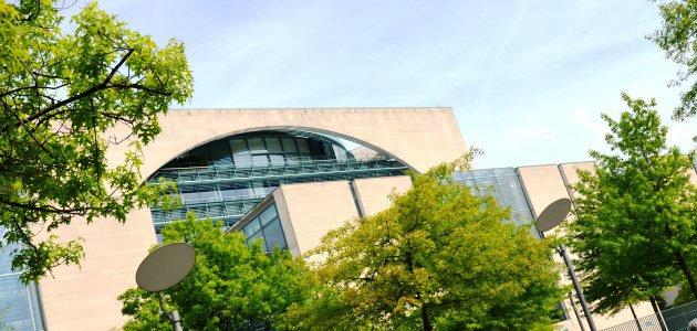 Durch das Laub zweier Bäume ist von schräg unten die Längsfassade des Bundeskanzleramts in Berlin zu sehen.