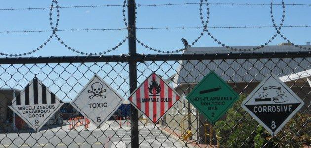 Das Bild zeigt einen Werkszaun mit Warnschildern.