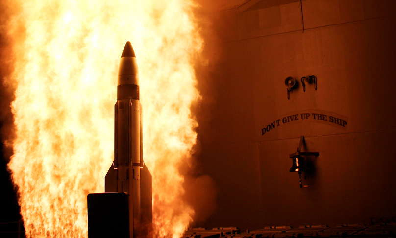 Eine Rakete verlässt vor einem Feuerschweif einen Startkanister eines Kriegsschiffs; daneben ist eine Schiffsglocke mit dem Motto des Schiffs erkennbar.