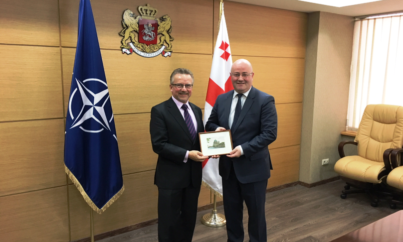 Zwei Herren in Anzügen stehen vor einer Flagge der NATO und einer Flagge Georgiens, schütteln die Hände und halten gemeinsam ein kleines gerahmtes Bild.