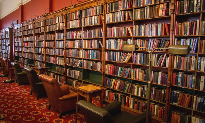 Von links hinten nach rechts vorn füllt ein nahezu wandhohes altes Bibliotheksregal voller Bücher das Bild aus; davor stehen Sessel.