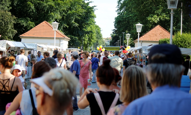 Eine Menschenmenge bewegt sich zwischen einer Reihe von Ständen, Luftballons in Schwarz Rot Gold sind zu sehen.