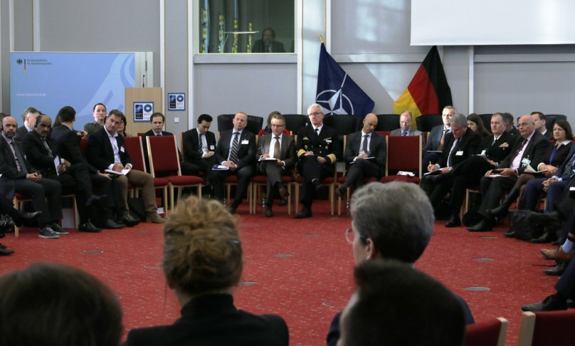A large group of both uniformed and business-dressed people are sitting in a large circle of chairs within the Federal Academy's Historic Hall.