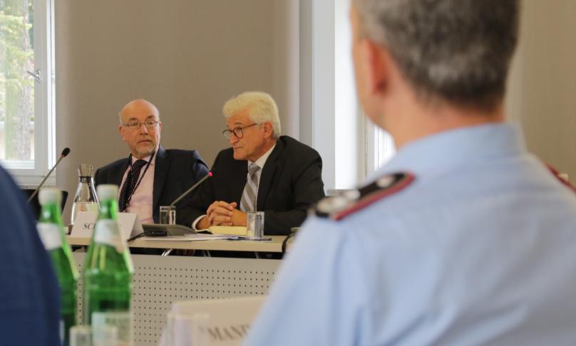 Zwei Herren im Anzug sitzen hinter Mikrofonen an einem Konferenztisch; der links im Bild blickt zu seinem Nachbarn; der rechts im Bild blickt in das Plenum.