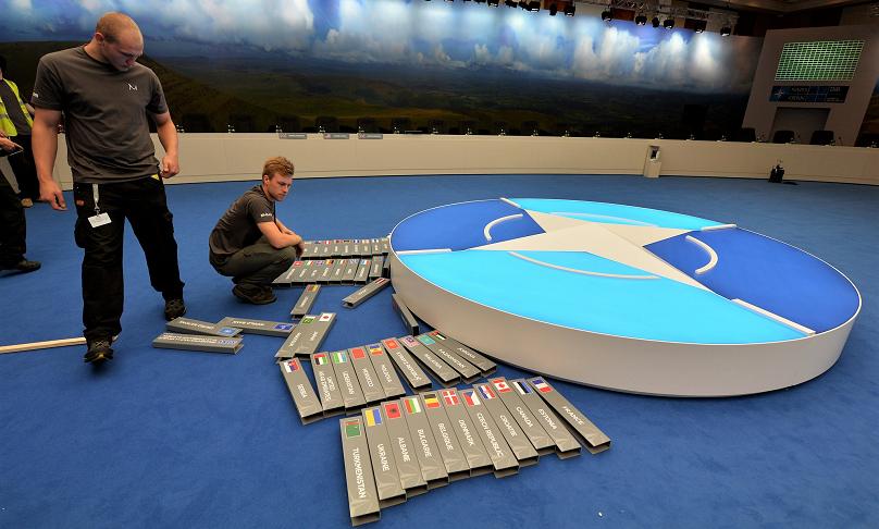 Zwei Handwerker bauen bei einer NATO-Tagung einen Konferenztisch auf; die Tischschilder mit den Flaggen der teilnehmenden Staaten liegen noch auf dem Boden.