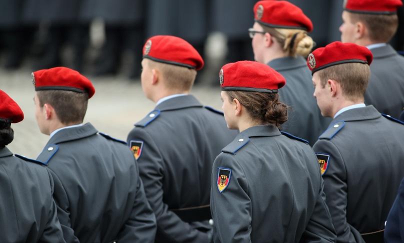 Uniformierte Soldatinnen und Soldaten stehen in Reih und Glied.