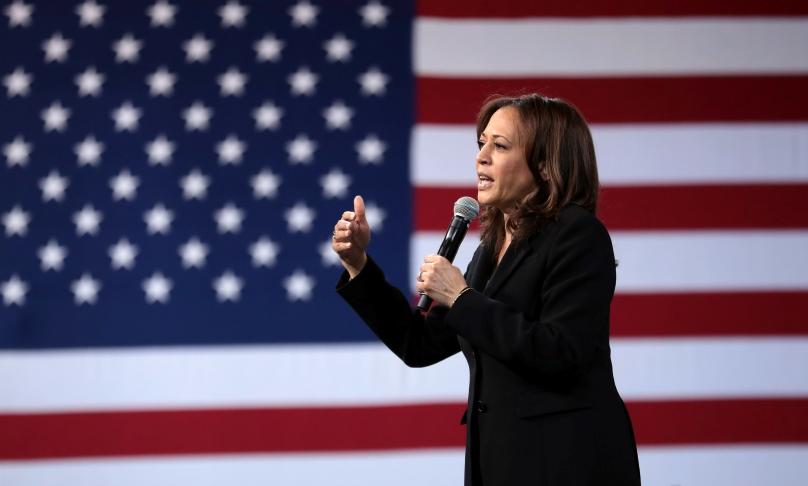 Das Foto zeigt die US-Senatorin Kamala Harris mit einem Mikrofon in der Hand sprechend vor einer Flagge der USA.