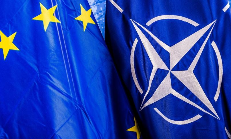 Das Bild zeigt zwei aneinanderliegende Flaggen, nämlich jene der NATO und der EU.