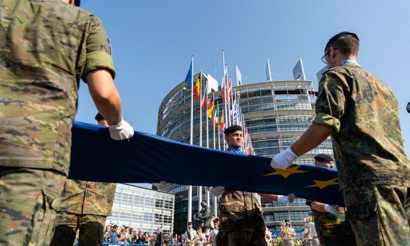Vor dem Europaparlament wehen europäische Nationalflaggen; im Vordergrund halten Soldaten eine EU-Flagge.