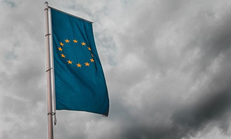 Vor einem wolkenverhangenen Himmel ragt eine Flagge der EU empor.