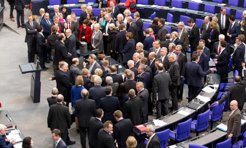 Abgeordnete des deutschen Bundestages stehen um die Ja und Nein Wahlurnen und geben ihre Stimme ab.